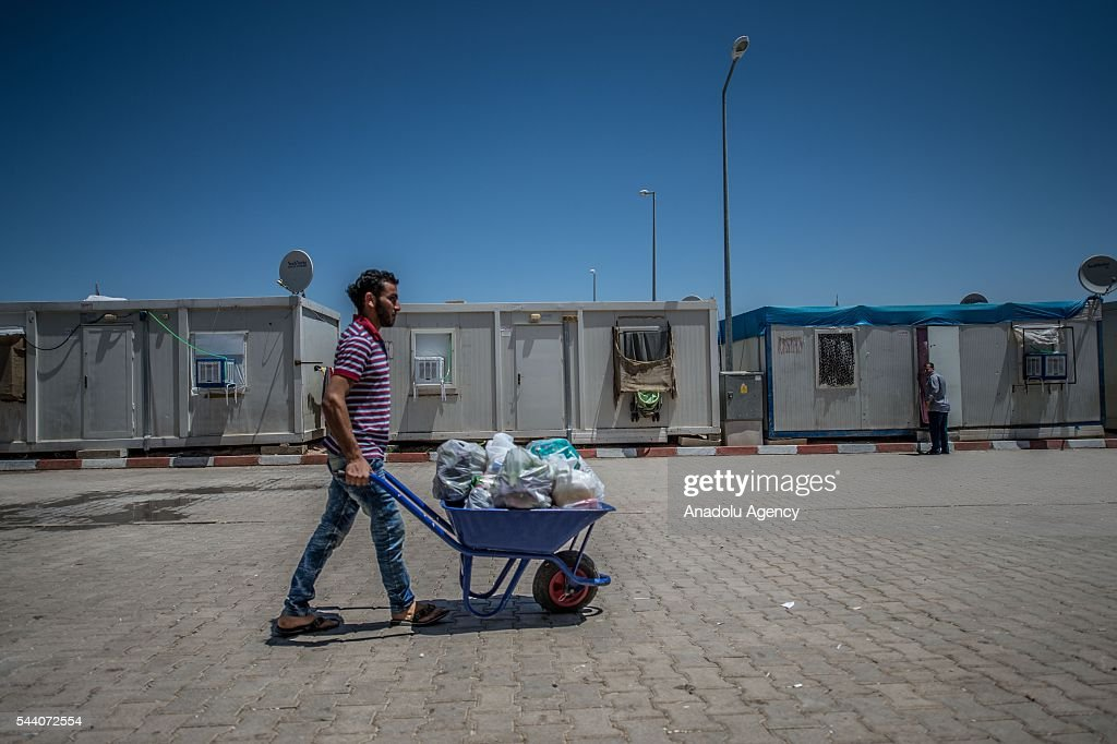 Syrian refugee man carries grocery bag with wheelbarrow at refugee camp grocery in Suruc district of Sanliurfa, Turkey on July 01, 2016, as the Syrian people who fled the clashes between Daesh and Kurdish armed groups about two years ego, make preparations for the Eid al-Fitr marks the end of the Muslim holy fasting month of Ramadan by preparing sweets despite the all harsh conditions at the camp away from their home.