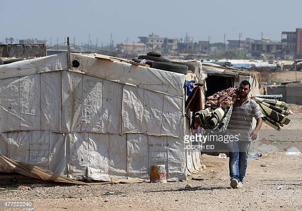 A Syrian refugee man carries his matresses at an unofficial refugee camp in the area of Arida north of Beirut on June 15 2015 Rights group Amnesty...