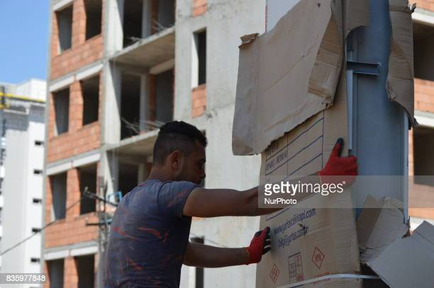 A Syrian refugee man lifts up a new door at a construction site in the Anayurt neighbourhood of Ankara Turkey on August 20 2017