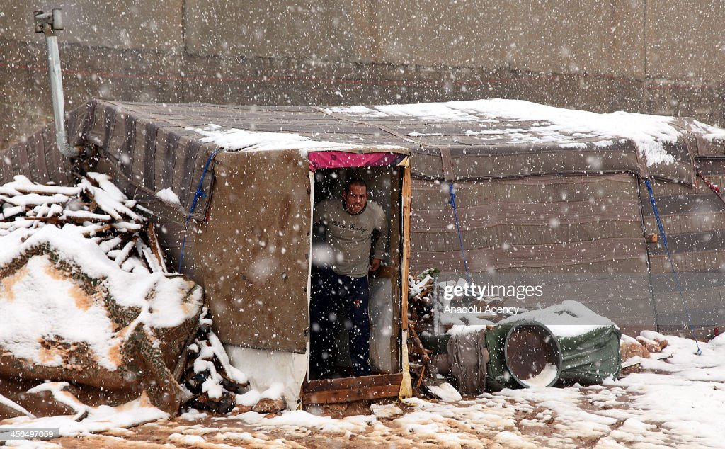 A Syrian refugee man looks out of his makeshift tent in Amman, Jordan on December 12, 2013. Nearly 140 Syrian refugee families living at makeshift tents in southern Amman struggle to survive in harsh winter conditions.