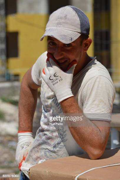 A Syrian refugee man poses for a picture as he works at a construction site in the Anayurt neighbourhood of Ankara Turkey on August 20 2017