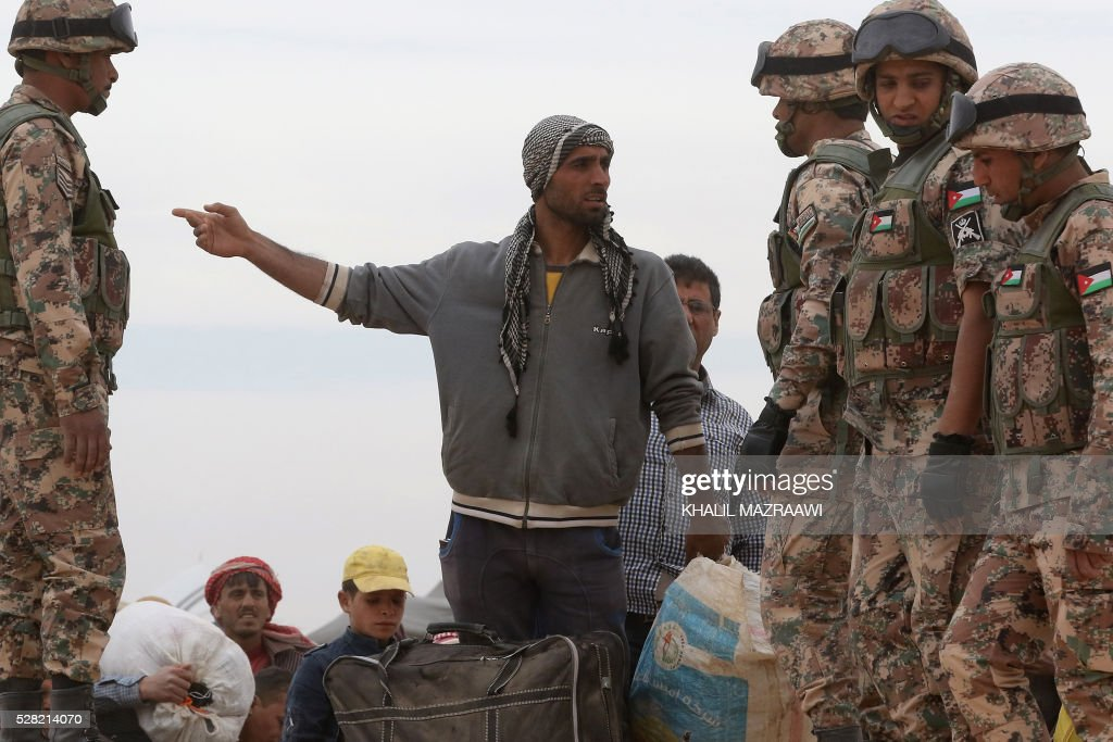 A Syrian refugee man speaks with a member of the Jordanian army as he waits to cross to the Jordanian side of the Hadalat border crossing, a military zone east of the capital Amman, after arriving from Syria on May 4, 2016. According to the Jordanian Commander of the Border Guards Brigadier Saber Al-Mahayreh, around 5000 Syrians fleeing from recent attacks on the northern Syrian city of Aleppo are trying to cross into Jordan in search of safety, most of whom are exhausted and desperately in need of help and medical treatment. MAZRAAWI