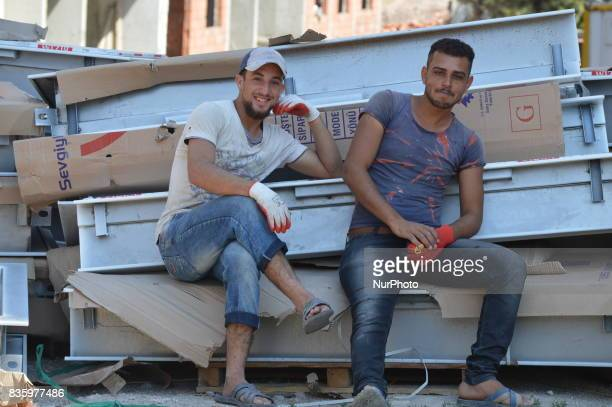 Syrian refugee men pose for a picture as they work at a construction site in the Anayurt neighbourhood of Ankara Turkey on August 20 2017