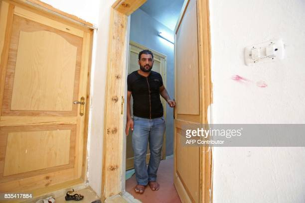 Syrian refugee Mohamed Ghazal opens the door of a home in the northern Jordanian city of Irbid where his family is being housed under a programme...