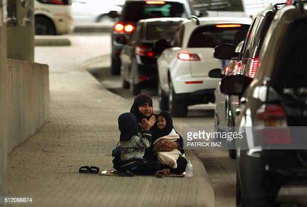 A Syrian refugee plays with her children as she sits begging under a bridge in the town of Jdeideh north east of the Lebanese capital Beirut on...