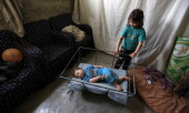 A Syrian refugee plays with her sibling in their home at Dalhamiyah camp for Syrian refugees in the Lebanese Bekaa valley on May 29 2014 Lebanon said...