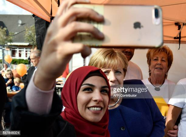 A syrian refugee poses for a selfie photo with German Chancellor Angela Merkel as she continued on the election campaign trail in Stralsund on...