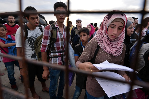 A Syrian refugee prepares her family's papers as they queue to board a ferry bound for the Piraeus harbour at the port of Kos, on the Aegean island of Kos, on August 14, 2015