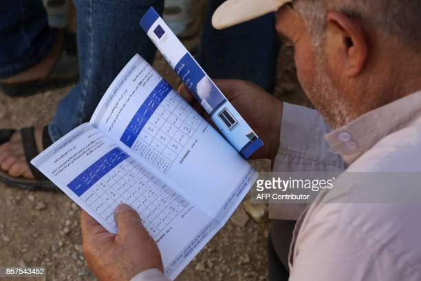 A Syrian refugee reads a pamphlet as he waits to register his name at the Zaatari office for employment on October 4 2017 at the Zaatari refugee camp...