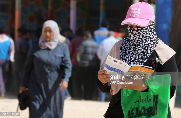 A Syrian refugee reads a pamphlet for employment on October 4 2017 at the Zaatari refugee camp 80 kilometres north of the Jordanian capital Amman...