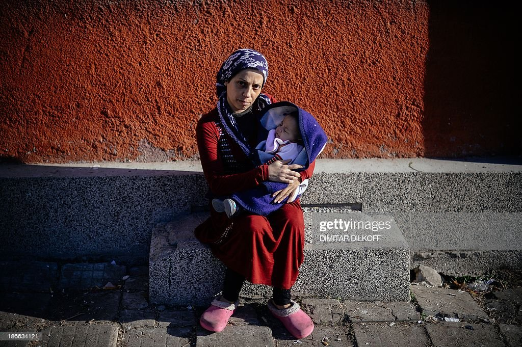Syrian refugee Siham, 30, from Aleppo, poses for a photo with her baby on October 26, 2013 at the recently opened Voenna Rampa shelter, a former school that now houses some 600 refugees in Sofia.