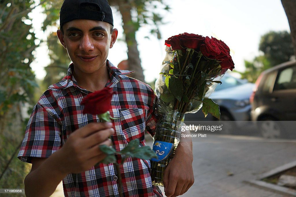A Syrian refugee teen sells flowers along the corniche on June 26, 2013 in Beirut, Lebanon. Cosmopolitan Beirut, which has for centuries been a melting pot of diversity in the Middle East, is facing tensions due to the influx of Syrian refugees that are straining social services. Fighting between supporters of the rebels in Syria and the Iranian backed Hezbollah movement has intensified in the cities of Sidon and Tripoli as the Syrian civil war continues to destabilize neighboring countries.