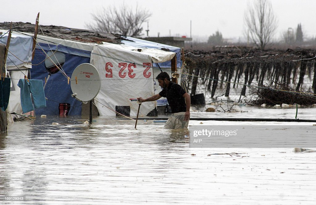 A Syrian refugee wades through flood waters close to a tent and washing line in the eastern Lebanese Bekaa Valley, on January 8, 2013, as stormy weather sparked widespread flooding, prompting chaos on the roads and a nationwide school closure for the next two days. The number of Syrian refugees in Lebanon is already totalling 156,000, according to UN figures, and 200,000 according to the Lebanese government estimates. AFP PHOTO /HASSAN JARAH