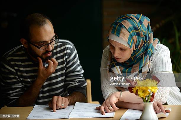 Syrian refugee Wael AlAwis left and his wife Reem Haskour study their documents they received from the Germany government at the community center of...
