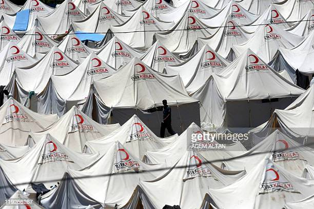 A Syrian refugee walks in a refugee camp in the Turkish border town of Yayladagi in Hatay province on June 25 2011 Thousands of Syrians have fled to...