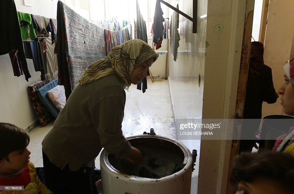 A Syrian refugee washes clothes as she takes shelter with her family at the Taqi Al-Din school in the Dumar neighbourhood of Damascus on February 26, 2013. The Syrian conflict has already claimed more than 70,000 lives in the two years since President Bashar al-Assad's crackdown on anti-regime protesters, leaving another two million people internally displaced and forcing 870,000 refugees to flee to neighbouring states.