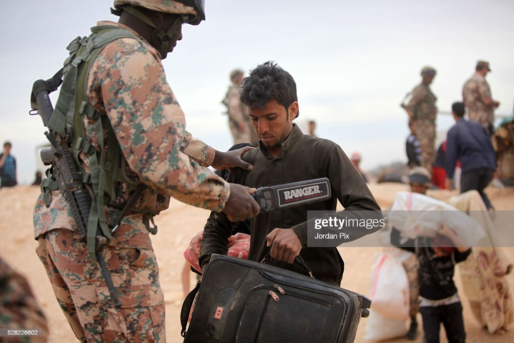 A Syrian refugee who has arrived at the Jordanian military crossing point of Hadalat at the border with Syria is checked with a metal detector before crossing into Jordan after a long walk through the Syrian desert on May 4, 2016 in Hadalat, Jordan. Coming from the cities of Raqaa, Deir Al-Zor and Hama, roughly 300 hundred refugees crossed into Jordan at Hadalat on Wednesday, while over 5000 refugees crossed in the last four days coming from Aleppo.