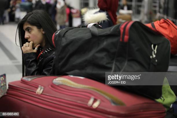 A Syrian refugee who is a part of a group of Syrians who were granted humanitarian visas by the Italian government waits at the departures hall in...