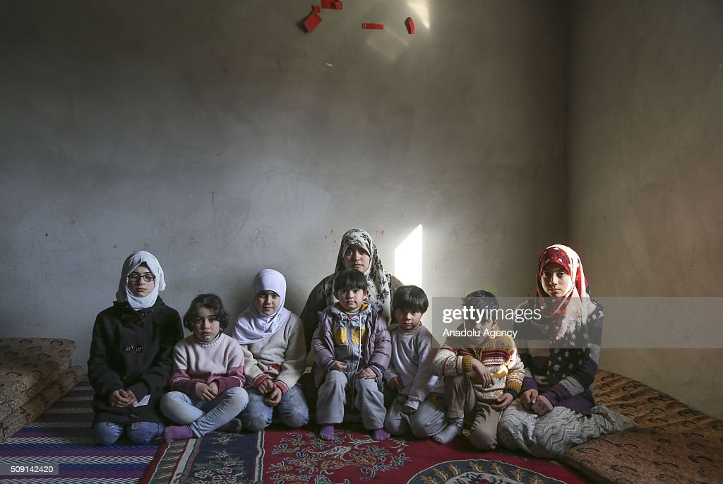 Syrian refugee widow mother Emira Said (Rear), fled from Syria due to ongoing civil-war, poses with her 7 children at a house in Turkey's Syrian border city Hatay's Reyhanli District on February 08, 2016. Emira Said had lost her husband due to a Assad Regime's barrel bomb attack. Turkey spent US$ 8 Billion and hosts approximately 2 million refugees.