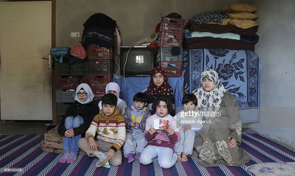 Syrian refugee widow mother Emira Said (R), fled from Syria due to ongoing civil-war, poses with her 7 children at a house in Turkey's Syrian border city Hatay's Reyhanli District on February 08, 2016. Emira Said had lost her husband due to a Assad Regime's barrel bomb attack. Turkey spent US$ 8 Billion and hosts approximately 2 million refugees.