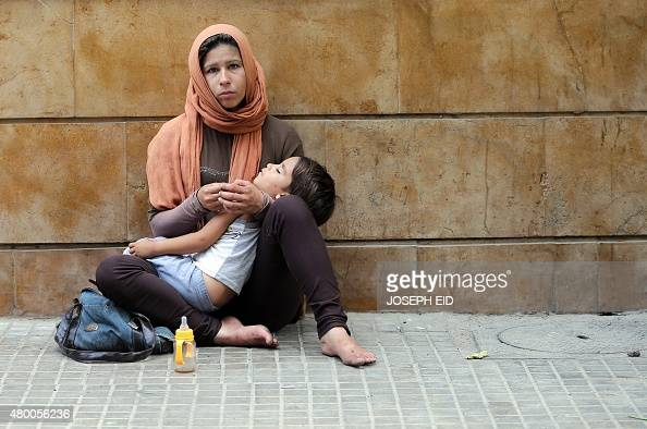A Syrian refugee woman begs for money on the pavement of a street in the Lebanese capital Beirut on July 9 2015 More than four million Syrians have...