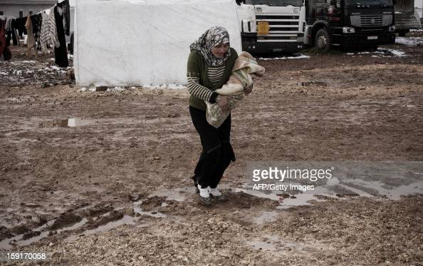 A Syrian refugee woman carries her child at a refugee camp near the northern city of Azaz on the SyriaTurkey border on January 9 2013 The internally...