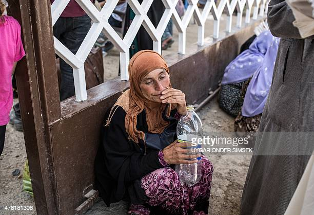 A Syrian refugee woman drinks water as she waits to cross the SyriaTurkey border on June 22 to return to the northern Syrian town of Tal Abyad in...