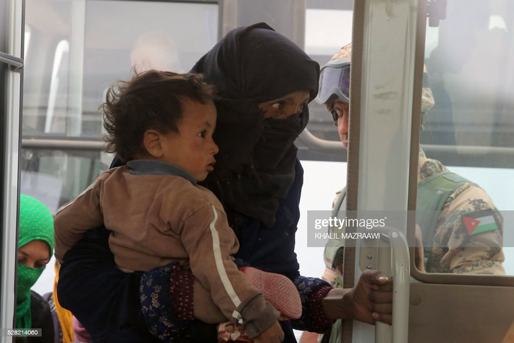 A Syrian refugee woman enters a bus as newly arrived refugees wait to cross to the Jordanian side of the Hadalat border crossing, a military zone east of the capital Amman, after arriving from Syria on May 4, 2016. According to the Jordanian Commander of the Border Guards Brigadier Saber Al-Mahayreh, around 5000 Syrians fleeing from recent attacks on the northern Syrian city of Aleppo are trying to cross into Jordan in search of safety, most of whom are exhausted and desperately in need of help and medical treatment. MAZRAAWI