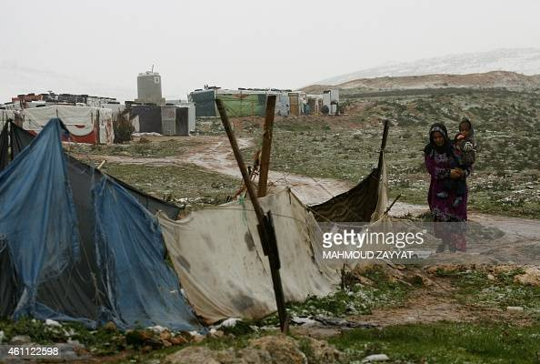 A Syrian refugee woman from the northwestern Syrian province of Idlib walks at a refugee camp in the southern Lebanese village of Ibl AlSaki on...