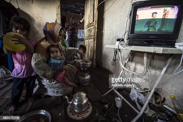 Syrian refugee woman living in an abandoned house wit her relatives heats the Iftar meals distributed by local municipalities and nongovernmental...