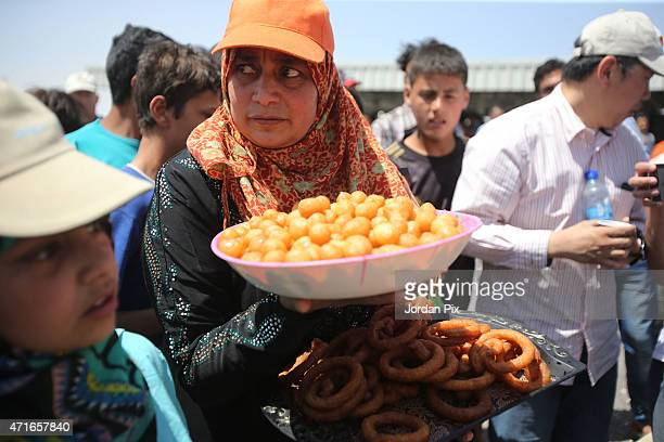 Syrian refugee woman offers some sweets to the guests at the souk in the AlAzraq camp for Syrian refugees on April 30 2015 in AlAzraq Jordan To...