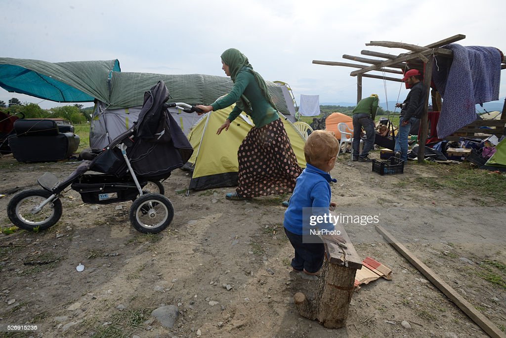 A Syrian refugee woman pushes a stroller as her baby plays on May 1'st, 2016 in Idomeni refugee camp. Humanitarian conditions in the camp are deteriorating as many thousands of migrants are still located in the makeshift refugee camp, located at the Greece-Macedonia border, waiting for the border to re-open.