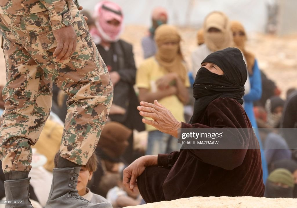 A Syrian refugee woman speaks with a member of the Jordanian army as she waits to cross to the Jordanian side of the Hadalat border crossing, a military zone east of the capital Amman, after arriving from Syria on May 4, 2016. According to the Jordanian Commander of the Border Guards Brigadier Saber Al-Mahayreh, around 5000 Syrians fleeing from recent attacks on the northern Syrian city of Aleppo are trying to cross into Jordan in search of safety, most of whom are exhausted and desperately in need of help and medical treatment. MAZRAAWI