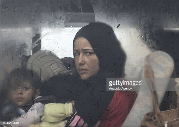 Syrian refugee woman together with her children looks outside from a window of a vehicle as she enters Reyhanli town of Hatay Turkey on October 28...