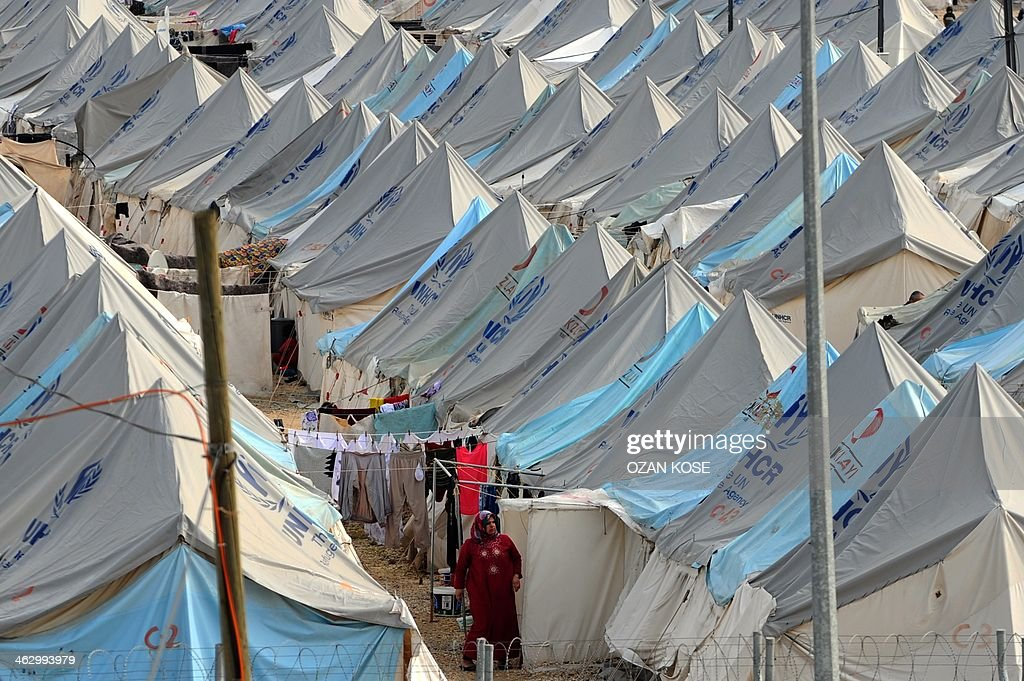 A Syrian refugee woman walks among tents at Karkamis' refugee camp on January 16 2014 near the town of Gaziantep south of Turkey Two weeks of battles...