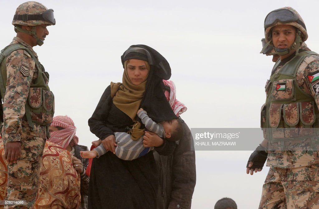 A Syrian refugee woman walks holding a baby between members of the Jordanian army as she waits to cross to the Jordanian side of the Hadalat border crossing, a military zone east of the capital Amman, after arriving from Syria on May 4, 2016. According to the Jordanian Commander of the Border Guards Brigadier Saber Al-Mahayreh, around 5000 Syrians fleeing from recent attacks on the northern Syrian city of Aleppo are trying to cross into Jordan in search of safety, most of whom are exhausted and desperately in need of help and medical treatment. MAZRAAWI