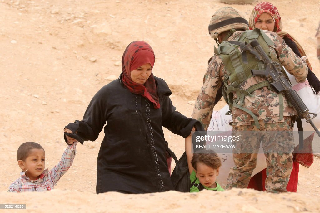 A Syrian refugee woman walks holding the hands of children as she waits to cross to the Jordanian side of the Hadalat border crossing, a military zone east of the capital Amman, after arriving from Syria on May 4, 2016. According to the Jordanian Commander of the Border Guards Brigadier Saber Al-Mahayreh, around 5000 Syrians fleeing from recent attacks on the northern Syrian city of Aleppo are trying to cross into Jordan in search of safety, most of whom are exhausted and desperately in need of help and medical treatment. MAZRAAWI