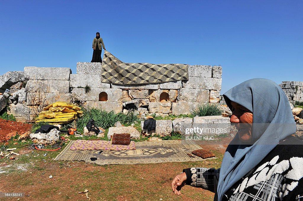 A Syrian refugee woman walks past her make shift home in the ruins of the ancient Roman city of of Serjilla, in the northwestern province of Idlib, on March 20, 2013. The number of Syrian refugees, already past the million mark, could double or triple by the end of the year if no solution is found to the conflict, the UN High Commissioner for Refugees Antonio Guterres said earlier this month.
