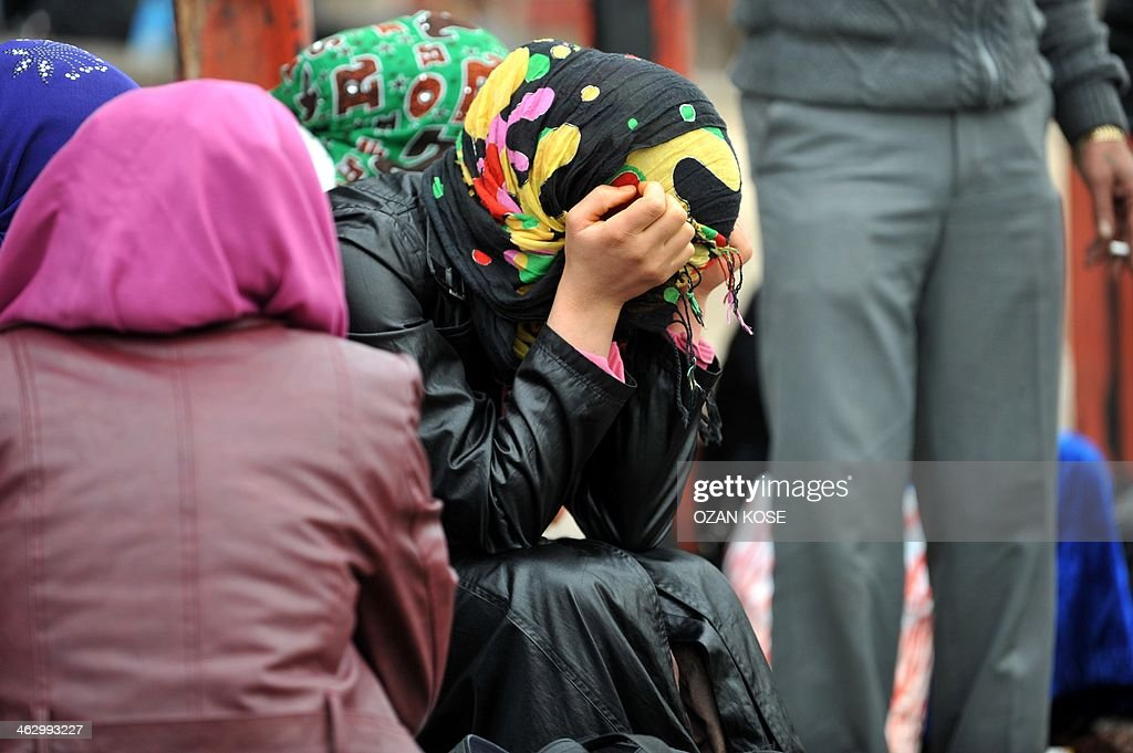 Syrian refugee women wait after crossing the Syrian border on January 16 2014 in Karkamis near the town of Gaziantep south of Turkey Two weeks of...