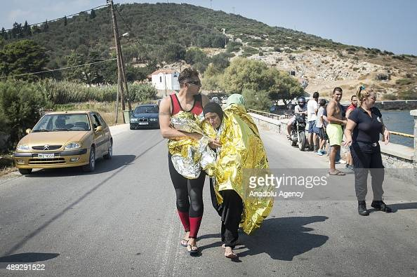 Syrian refugee women wrapped in a thermal blanket around them are taken to hospital upon their arrival on the coast of Lesbos Island Greece after...