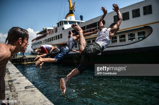 Syrian refugee youth dive into the Bosphorus during a warm summer day on August 13 2017 at Karakoy Port in the Turkish city of Istanbul as the Galata...