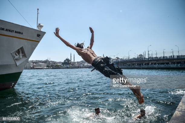 Syrian refugee youth dives into the Bosphorus during a warm summer day on August 13 2017 at Karakoy Port in the Turkish city of Istanbul as the...