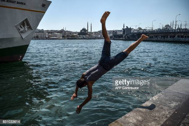 A Syrian refugee youth dives into the Bosphorus during a warm summer day on August 13 2017 at Karakoy Port in the Turkish city of Istanbul as the...