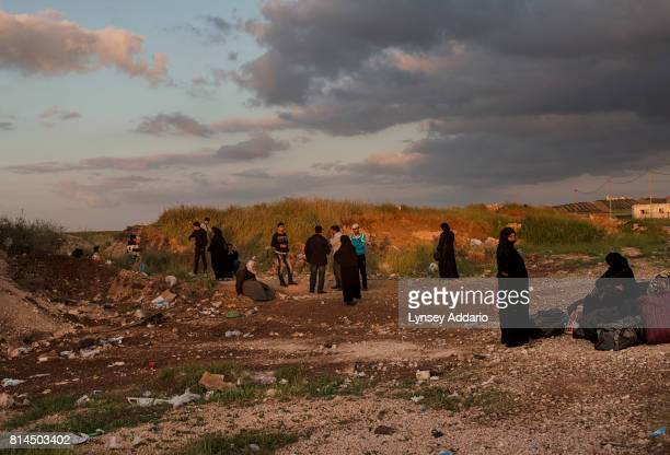 Syrian refugees are held by the Jordanians for questions regarding their identities at an unofficial crossing point at the border between Syria and...