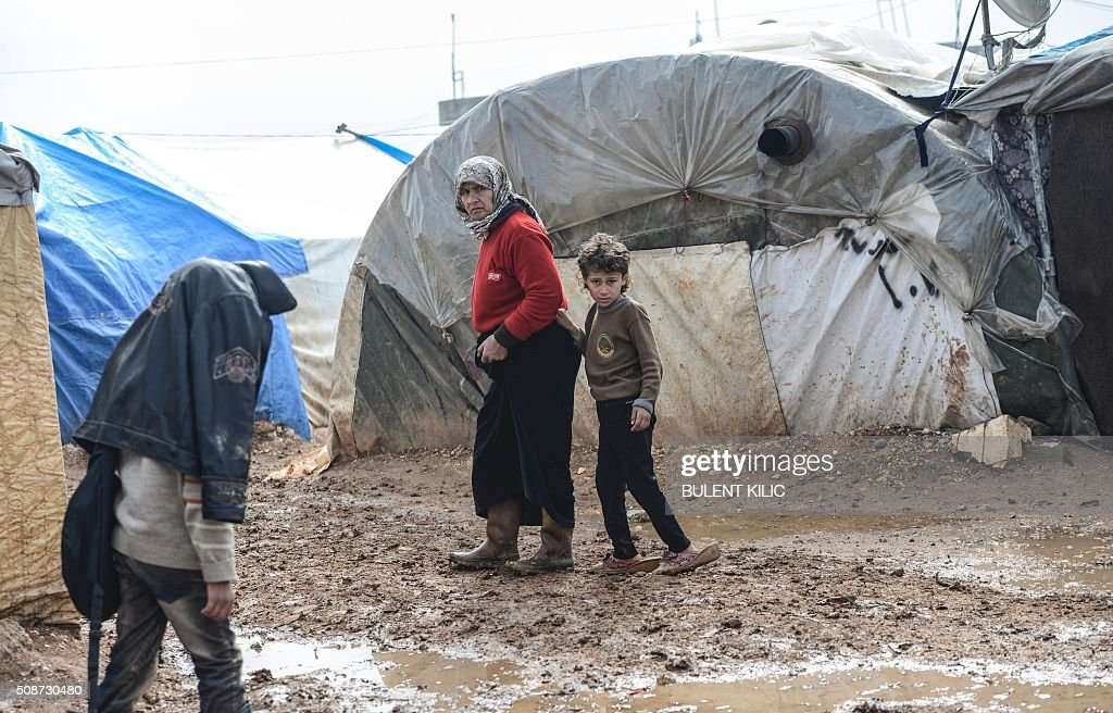 Syrian refugees are pictured in a camp as Syrians fleeing the northern embattled city of Aleppo wait on February 6, 2016 in Bab al-Salam, near the city of Azaz, northern Syria, near the Turkish border crossing. Thousands of Syrians were braving cold and rain at the Turkish border Saturday after fleeing a Russian-backed regime offensive on Aleppo that threatens a fresh humanitarian disaster in the country's second city. Around 40,000 civilians have fled their homes over the regime offensive, according to the Syrian Observatory for Human Rights monitor. / AFP / BULENT KILIC
