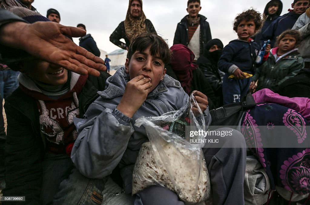 Syrian refugees are pictured in a camp as Syrians fleeing the northern embattled city of Aleppo wait on February 6, 2016 in Bab al-Salam, near the city of Azaz, northern Syria, near the Turkish border crossing. Turkey on Saturday said it was expecting a huge wave of Syrians fleeing a government onslaught on rebel-held territory, with a regional governor saying at least 70,000 people may be heading for the border. The United Nations said some 20,000 people had gathered at Syria's Bab al-Salam crossing with Turkey. An AFP reporter said the crossing was closed but the Syrian side of it was being supplied by aid trucks coming from Turkey. KILIC