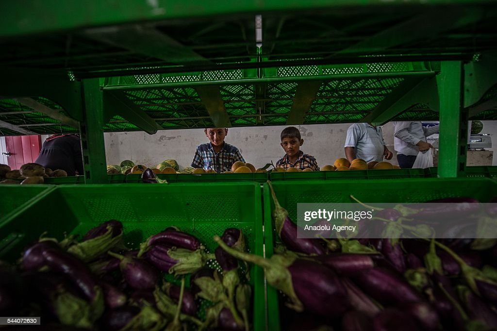 Syrian refugees are seen at refugee camp grocery in Suruc district of Sanliurfa, Turkey on July 01, 2016, as the Syrian people who fled the clashes between Daesh and Kurdish armed groups about two years ego, make preparations for the Eid al-Fitr marks the end of the Muslim holy fasting month of Ramadan by preparing sweets despite the all harsh conditions at the camp away from their home.