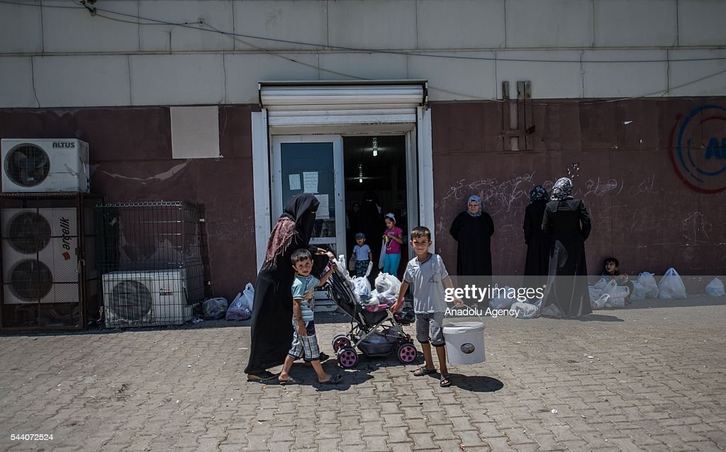 Syrian refugees are seen in front of refugee camp grocery in Suruc district of Sanliurfa, Turkey on July 01, 2016, as the Syrian people who fled the clashes between Daesh and Kurdish armed groups about two years ego, make preparations for the Eid al-Fitr marks the end of the Muslim holy fasting month of Ramadan by preparing sweets despite the all harsh conditions at the camp away from their home.