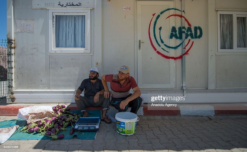 Syrian refugees are seen in front of shelter at refugee camp grocery in Suruc district of Sanliurfa, Turkey on July 01, 2016, as the Syrian people who fled the clashes between Daesh and Kurdish armed groups about two years ego, make preparations for the Eid al-Fitr marks the end of the Muslim holy fasting month of Ramadan by preparing sweets despite the all harsh conditions at the camp away from their home.