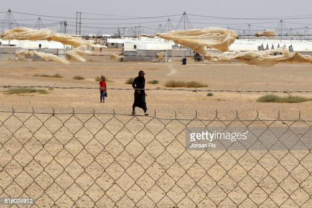 Syrian refugees are seen walking out of the innovation center that is run by Relief International and the unicef under the hot sun near his makeshift...